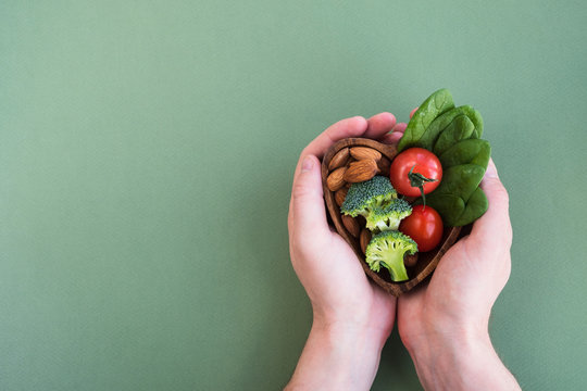 Healthy food for heart on green background. Man hands hold plate with vegetables, spinach and nuts. Diet, superfood and health concept. Top view, flat lay, copy space