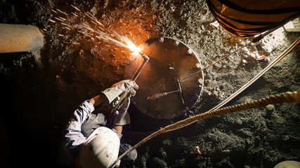 Man doing oxy-acetylene cutting inside confined space with blower ducting and lifeline.