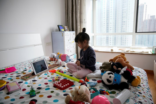 Lin Wowo, 5, talks to her friend through Facetime on an iPad inside a bedroom in her home in Shanghai