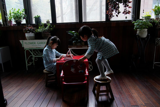 Sisters Yao Yicheng, 6, and Yao Yihang, 4, learn Chinese on an iPad at a balcony of their home in Shanghai