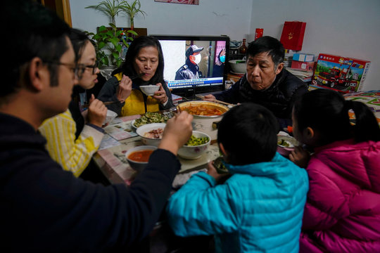 The Cai family are seen at dinner, as a TV broadcasts news on the coronavirus in the living room of their home in Shanghai