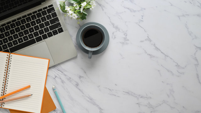 Top view image of marble table with accessories putting on it. Flat lay Computer laptop, Ceramic coffee cup, potted plant, notebook and pencil. Orderly/Comfortable workplace concept.