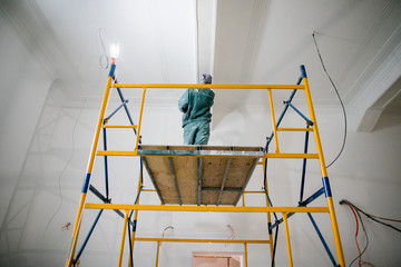 repair of premises, the builder works with plaster on scaffolding