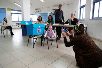 A woman photographs her baby at a polling station as Israelis vote in a national election, in the Israeli settlement of Nokdim, in the occupied West Bank