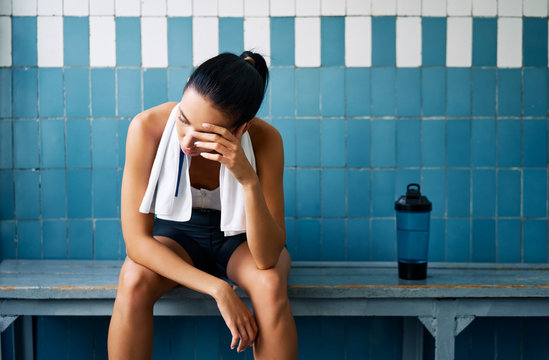 Tired fit woman with a towel in the locker room after hard workou
