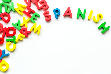 Learn Spanish. Concept with letters on white background top-down copy space