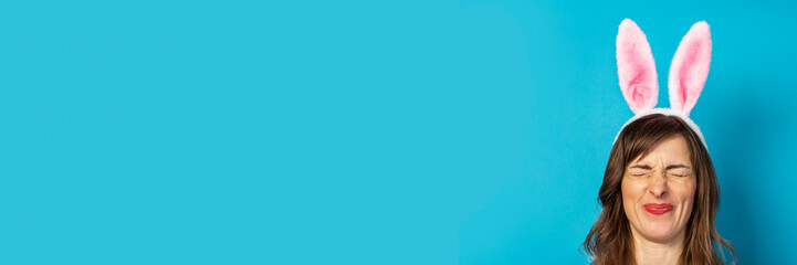 Young woman with closed eyes and ears of a rabbit on a blue background. Easter concept, surprise, hide and seek. Banner