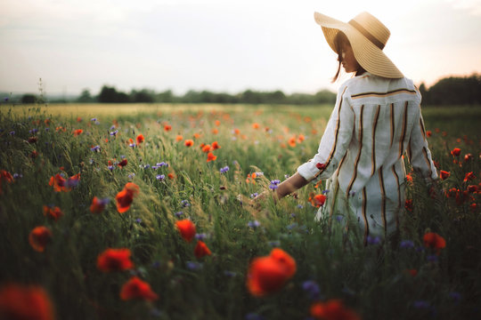 Stylish woman in rustic linen dress walking in summer meadow among poppy and wildflowers in sunset light. Atmospheric authentic moment.Copy space. Girl in hat in countryside. Rural slow life.