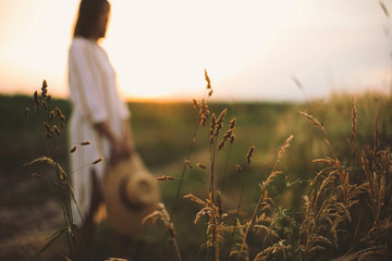 Herbs and grasses in sunset light on background of blurred woman in summer meadow. Wildflowers close up in warm light and rustic girl relaxing in evening in countryside. Tranquil moment Fotomurales