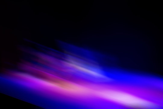 Abstract blurred color blurred dark background, purple, cyan, black and light spots.