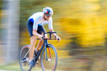 Panning shot of sportsman riding a bike in park Wall mural