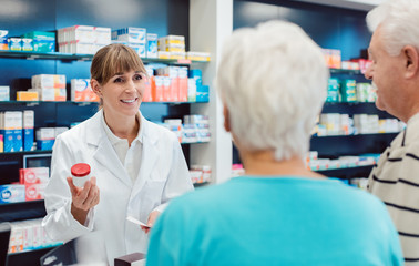 Foto op Canvas Apotheek Chemist advising senior couple on a drug in her pharmacy