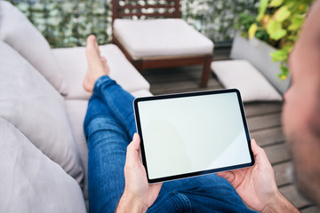 Close up of man lounging on patio and looking at tablet screen