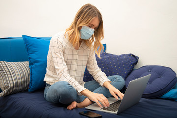 Young woman in quarantine for Corona virus wearing protective mask while smart working on sofa at home