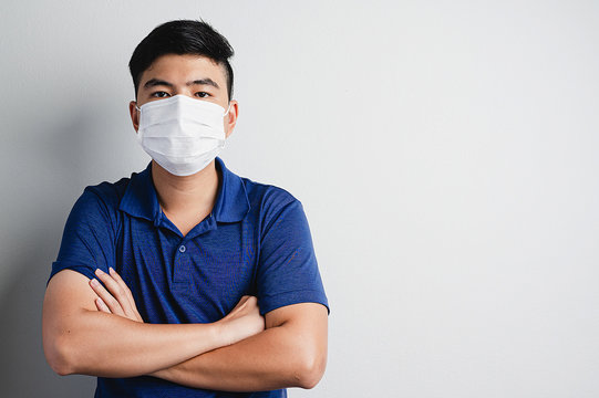 Asian smart, confident and healthy man wear medical mask to prevent pollution, virus in pain grey bakground.