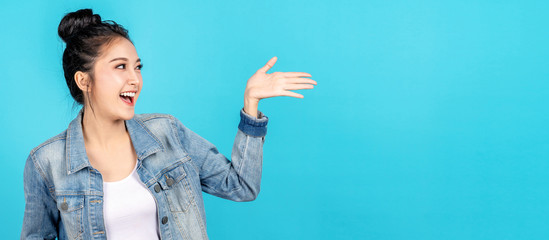 Banner of Happy asian woman feeling happiness and gesture hand open on blue background. Cute asia girl smiling wearing casual jeans shirt and present on copy space.