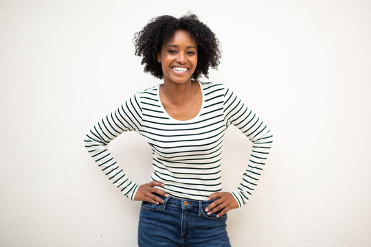 smiling young beautiful black woman with hands on hip against white background