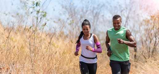 Happy African couple jogging in a autumn forest. Panoramic, Banner, Meadow, Dry, Grass, Nature.