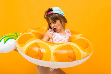 Beautiful little girl in swinsuit holds a rubber ring isolated on yellow and orange background Fototapete