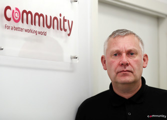 Paul Warren is pictured next to a Community trade union sign at his office in Middlesbrough