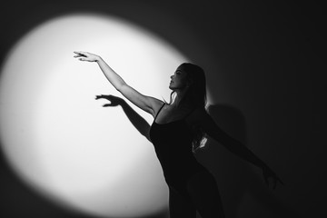 The girl is a dancer, a blonde in a black body, dances in the light of a searchlight, makes waved...