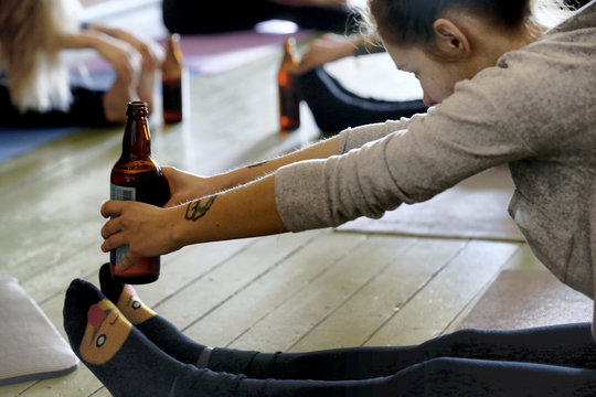 A woman holds a bottle as she performs beer yoga in Riga