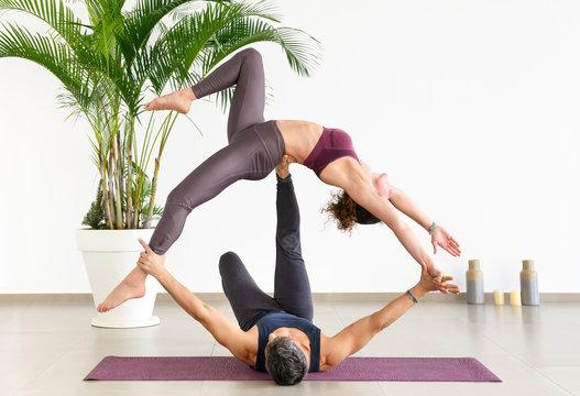 Two gymnasts doing an acroyoga pose
