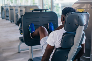 Back view of African American man doing exercise on leg press during fitness training in modern gym.