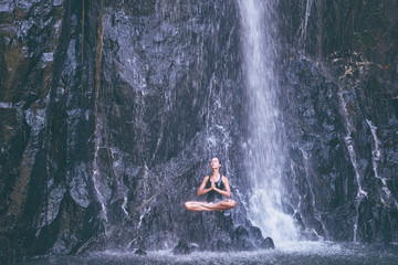Wellness spa, vacation and yoga meditation concept. Pretty young woman in swimsuit sitting in lotus position on the rock under tropical waterfall. Fotobehang