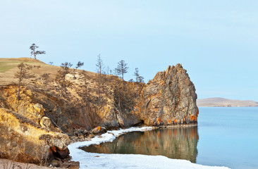 Deurstickers Canyon Baikal Lake in May day. White ice floes melt on the beach near the rocks of Olkhon Island. The Wish Tree - a beautiful larch with tourists ribbons on the hill. Spring landscape