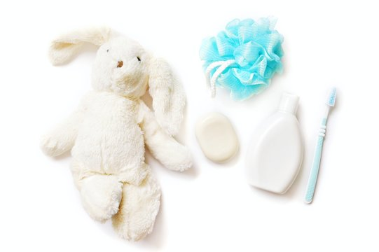 Flat lay natural organic bath products for kids. Toy rabbit, soap bar, shampoo bottle, toothbrush and blue sponge