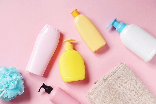 Baby care cosmetic products view from above photography. Blue sponge, shampoo bottle, shower gel packing, hair balm, conditioner, cotton towel on a pink background