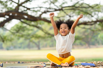 Happy African american little girl smiling and raises her hand while sitting in the park Fototapete