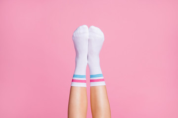 Cropped close-up view of nice vertical feminine legs wearing white casual soft cotton comfortable socks new brandy collection isolated over pink pastel color background