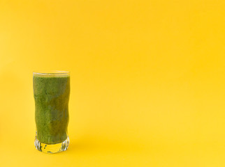 Smoothies of green herbs in a glass on a bright yellow background.
