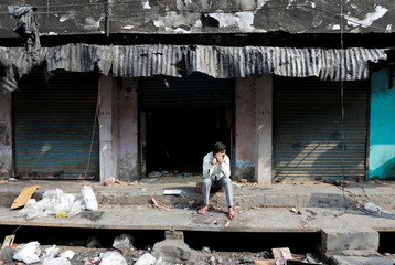 A man sits in front of burnt out properties owned by Muslims in a riot affected area following clashes between people demonstrating for and against a new citizenship law in New Delhi