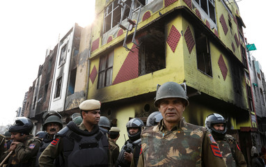 Policemen stand guard in front of burnt out properties owned by Muslims in a riot affected area following clashes between people demonstrating for and against a new citizenship law in New Delhi
