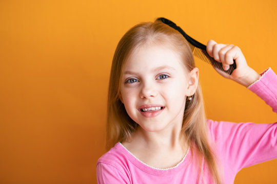 Cute baby, baby girl 6-8 years old combs her soft blond hair medium length comb and smiles on an orange background