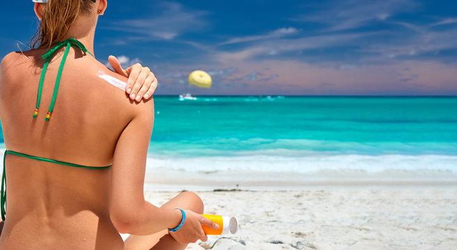 Tan woman on beach applying sunscreen