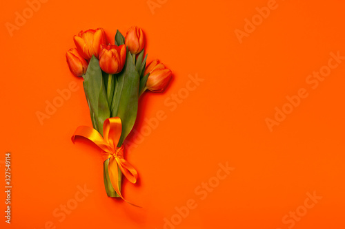Bouquet of tulips in orange and rich red colors. Concept of Women's Day, Mother's Day, 8 March, the holiday greetings. Copy space, flat lay.