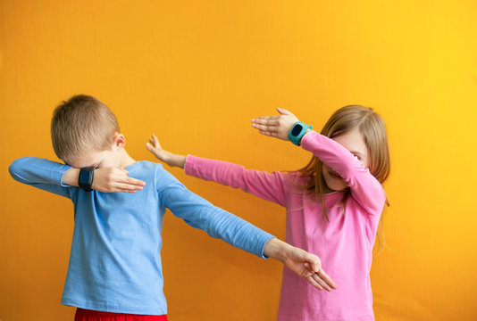 "Children 6-8 years old on an orange background with a smart GPS watch make a cool young gesture ""easy"""