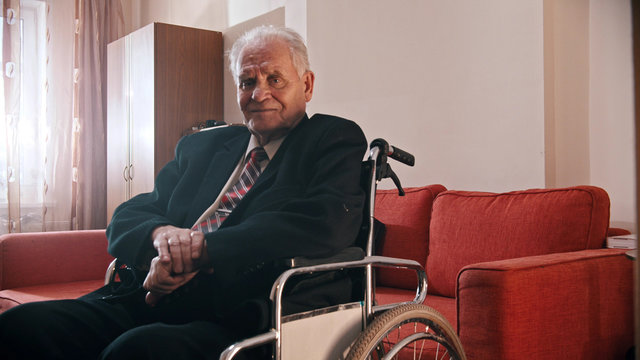 Elderly grandfather - smiling grandfather sitting in a wheelchair