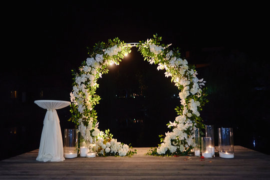 Night wedding ceremony with round arch, flowers, bulb lights and candles on the backyard outdoors, copy space. Wedding decor