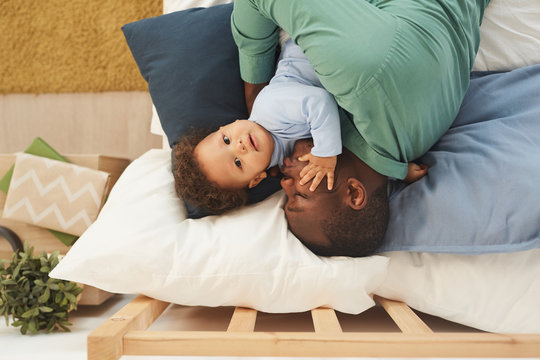 Above view portrait of adult African-American man embracing baby son while lying on bed at home, copy space