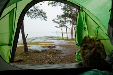 Fotorollo Olivgrun View from inside a tourist tent with backpack. Beautiful Scandinavian landscape of forest and rocky shore. Finland