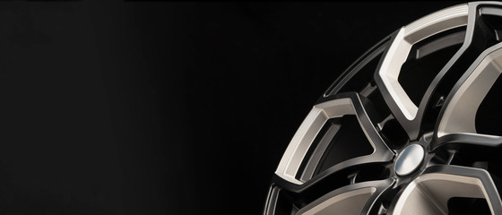aluminum alloy wheel. Premium cast, the design of the spokes and the wheel rim, a white and black elements on dark background close-up. long layout, copyspace