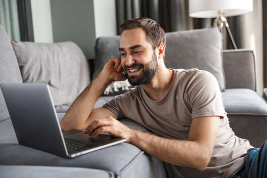 Man indoors at home on sofa using laptop computer.