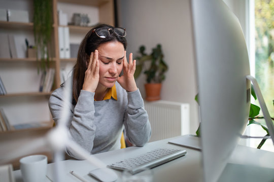 Businesswoman with headache at the desk indoors in office, feeling pain.