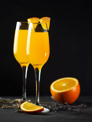 Mimosa drink with orange juice and champagne on a black background