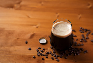 Obraz Craft beer coffee stout in a glass on a wooden table - fototapety do salonu